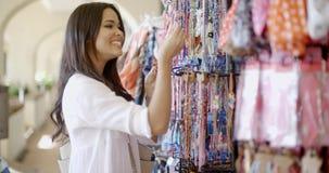 Frau, die Kleidung am Speicher wählt stock footage