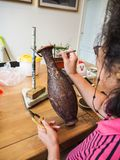 Frau, die kleine geformte Cloisonnedrähte zu einem kupfernen Vase klebt stockfotos