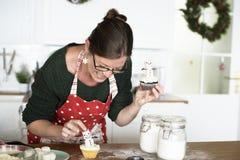 Frau, die kleine Kuchen für Weihnachten verziert Lizenzfreie Stockfotos