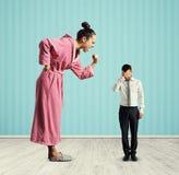Frau, die am kleinen müden Ehemann schreit Stockfoto
