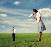 Frau, die am kleinen Mann auf dem Feld schreit lizenzfreie stockfotografie