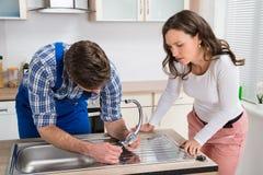 Frau, die Klempner Fixing Steel Tap betrachtet Stockfoto