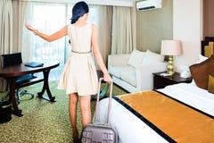 Frau, die Koffer im Hotelzimmer zieht Stockbild