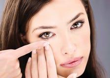 Frau, die Kontaktlinse in ihr Auge einsetzt Lizenzfreies Stockbild