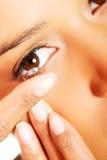 Frau, die Kontaktlinse in ihr Auge einsetzt Stockfotos