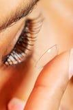 Frau, die Kontaktlinse in ihr Auge einsetzt Lizenzfreie Stockfotos