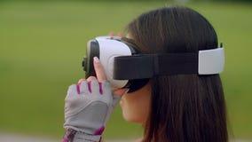 Frau, die Kopfhörer der virtuellen Realität im Park verwendet Asiatin, die VR-Gläser trägt stock video footage