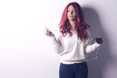 Frau, die Kopfhörer vom intelligenten Telefon verwendet lizenzfreie stockbilder