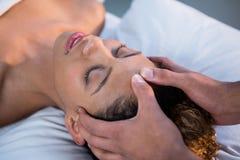 Frau, die Kopfmassage vom Physiotherapeuten empfängt Lizenzfreies Stockfoto