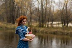 Frau, die Korb mit Äpfeln im Herbst im Freien hält Lizenzfreies Stockfoto
