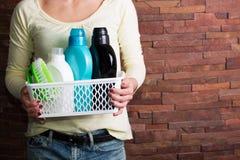 Frau, die Korb mit Reinigungsmitteln hält Lizenzfreie Stockbilder