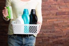 Frau, die Korb mit Reinigungsmitteln hält Lizenzfreies Stockbild