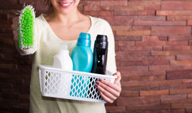 Frau, die Korb mit Reinigungsmitteln hält Stockbild