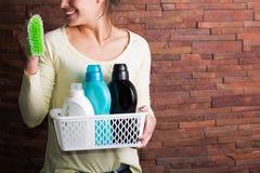 Frau, die Korb mit Reinigungsmitteln hält Stockfotos