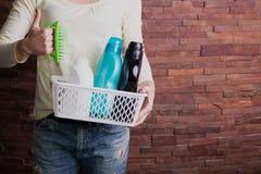 Frau, die Korb mit Reinigungsmitteln hält stockbilder