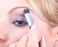 Frau, die Kosmetik mit Applikator aufträgt stockfoto