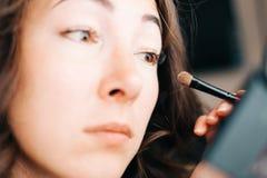 Frau, die Kosmetiklidschatten mit Bürste anwendet stockfotos
