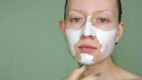 Frau, die kosmetische Maske auf ihrem Gesicht tut stock video footage