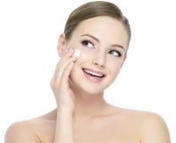 Frau, die kosmetische Sahne auf Gesicht aufträgt Stockbilder