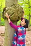 Frau, die krebsartigen Tumor auf Buchenbaum hält lizenzfreies stockfoto