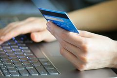 Frau, die Kreditkarte auf Laptop für on-line-Einkaufskonzept hält stockfotografie