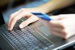 Frau, die Kreditkarte auf Laptop für on-line-Einkaufskonzept hält Lizenzfreies Stockfoto