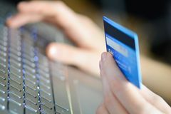 Frau, die Kreditkarte auf Laptop für on-line-Einkaufskonzept hält stockbilder