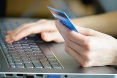 Frau, die Kreditkarte auf Laptop für on-line-Einkaufskonzept hält Lizenzfreies Stockbild