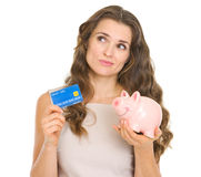 Frau, die Kreditkarte und piggy Querneigung anhält Lizenzfreie Stockfotografie
