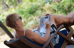 Frau, die Kreuzworträtsel tut Stockfotografie
