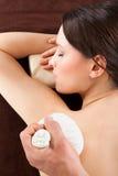 Frau, die Kräutermassage mit Stempeln am Badekurort empfängt Stockfoto