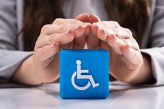 Frau, die Kubikblock mit behinderter Handikap-Ikone schützt lizenzfreie stockbilder