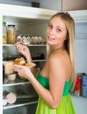 Frau, die Kuchen vom Kühlschrank isst Lizenzfreies Stockbild
