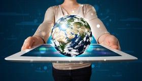 Frau, die Kugel der Erde 3d in der modernen Tablette darstellt Stockbilder