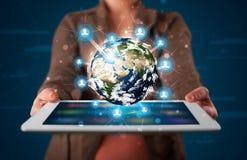Frau, die Kugel der Erde 3d in der modernen Tablette darstellt Lizenzfreie Stockfotografie