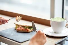 Frau, die Lachs-panini Sandwich am Restaurant isst stockbilder