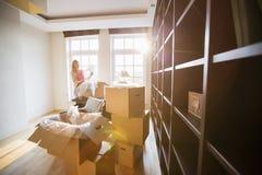 Frau, die Lampe von beweglichem Kasten am neuen Haus auspackt Lizenzfreie Stockfotos