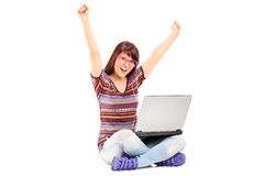 Frau, die an Laptop arbeitet und Erfolg gestikuliert Stockfotografie