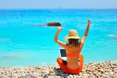 Frau, die Laptop auf dem Strand verwendet Stockbilder