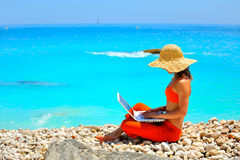 Frau, die Laptop auf dem Strand verwendet Lizenzfreies Stockbild