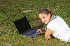 Frau, die Laptop auf Gras verwendet Stockbilder