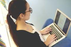 Frau, die an Laptop in der Bibliothek arbeitet Lizenzfreie Stockfotografie