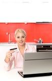 Frau, die Laptop in der Küche verwendet Stockbild