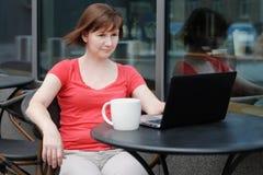 Frau, die Laptop in einem Café im Freien verwendet Stockfotografie