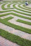 Frau, die Laptop in einem Kopfstein-Labyrinth verwendet stockbilder