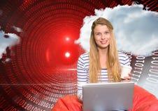 Frau, die Laptop gegen binären Hintergrund verwendet Lizenzfreie Stockfotografie