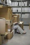 Frau, die Laptop im Büro-Lagerraum verwendet stockfotografie