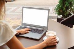 Frau, die Laptop mit leerem Schirm copyspace verwendet stockbilder