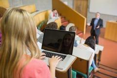 Frau, die Laptop mit Studenten und Lehrer am Vorlesungssal verwendet Stockbild