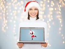 Frau, die Laptop mit Weihnachtsmann auf Schirm hält Lizenzfreies Stockbild